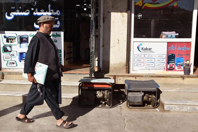 Un home camina pel davant de dos generadors que són a la vorera en un carrer de Kabul.