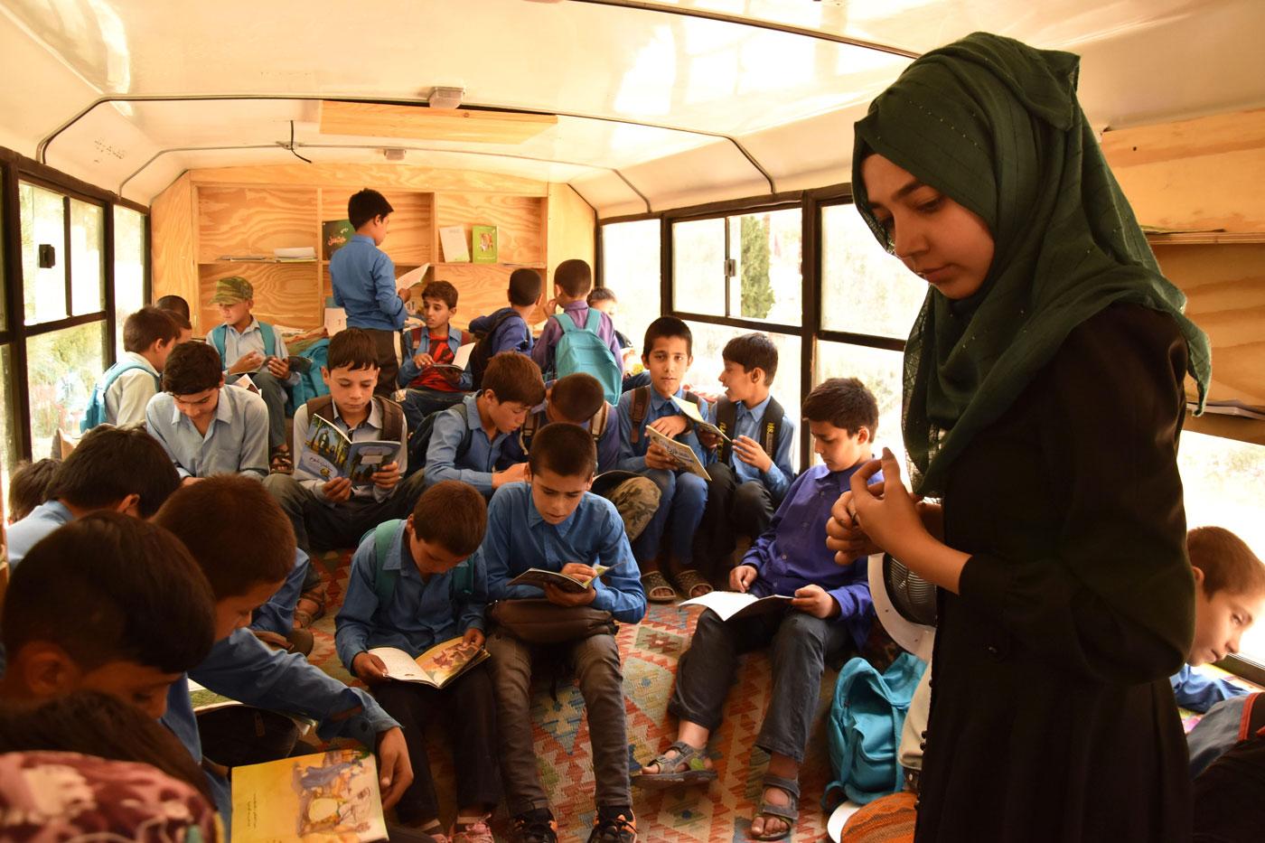 Una educadora comprova quins llibres estan llegint els nens en un dels autobusos de l'associació Charmaghz, aquest diumenge a Kabul.