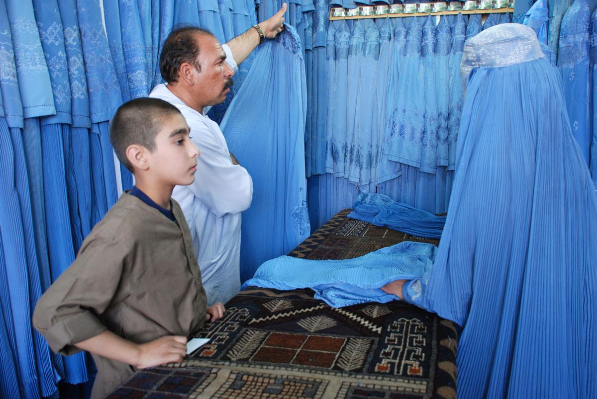 Un botiguer mostra un burca a una clienta. Moltes dones fan servir aquesta peça de  vestir a l'Afganistan.