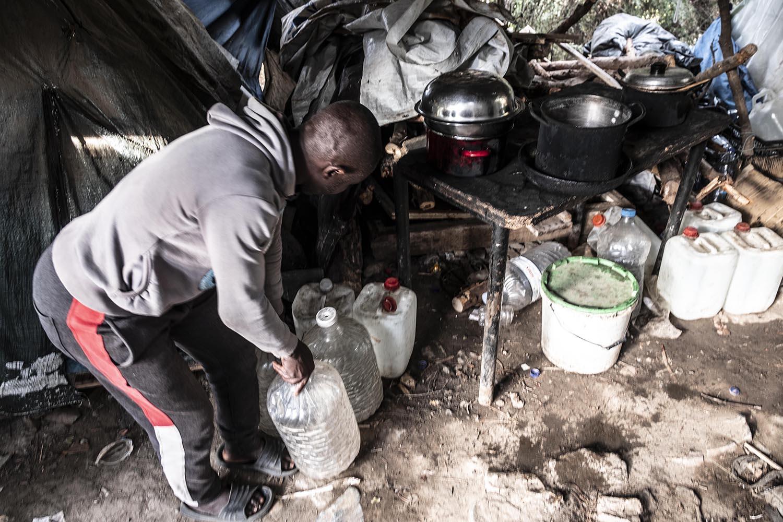 Un home de Ghana porta aigua a la cuina que comparteix amb mitja dotzena de compatriotes per fer el dinar del dia.