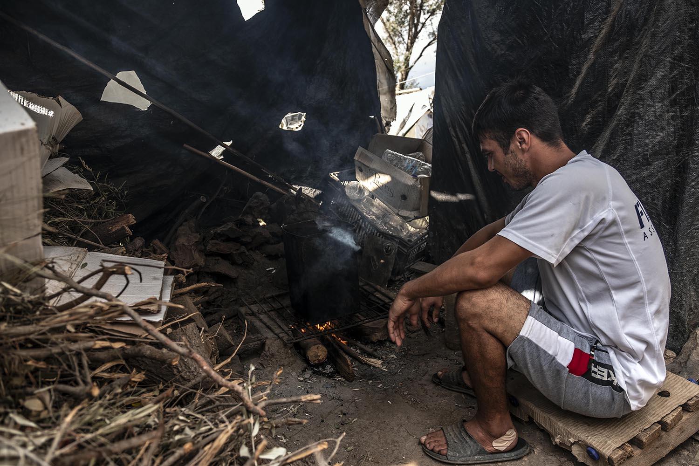 Un home kurd fa el dinar mentre per megafonia se senten advertiments de la prohibició de fer focs al camp.