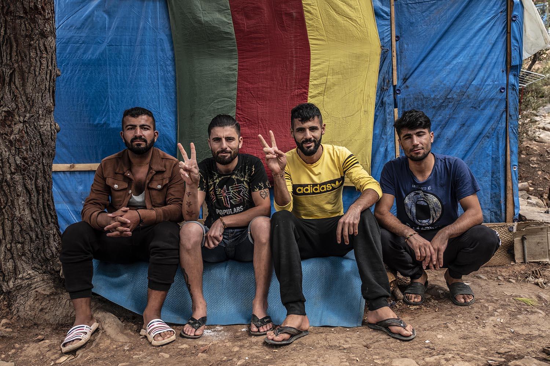 Saleh Ahmad (esquerra) amb altres companys kurds davant d'una bandera del Kurdistan que decora el lateral de la seva barraca.