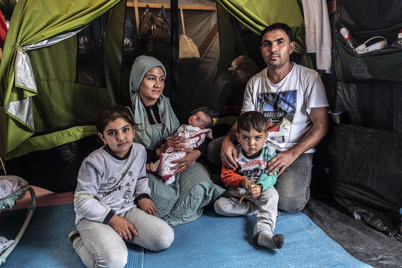 Afaf Bubi posa amb la seva família i la Maria, d'un mes, a la seva barraca, on han posat una tenda dins la construcció de fusta.