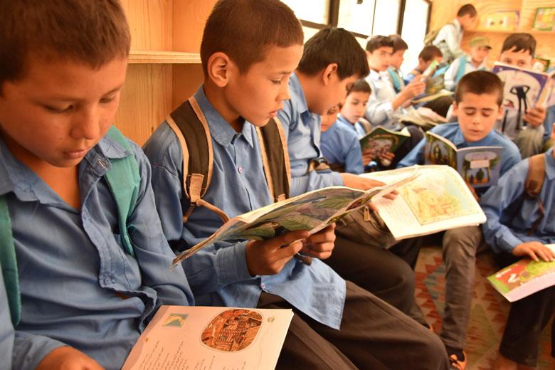 Alguns nens, llegint llibres a l'autobús biblioteca.