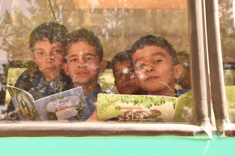 Uns infants miren per la finestra des d'un dels autobusos de Charmaghz.