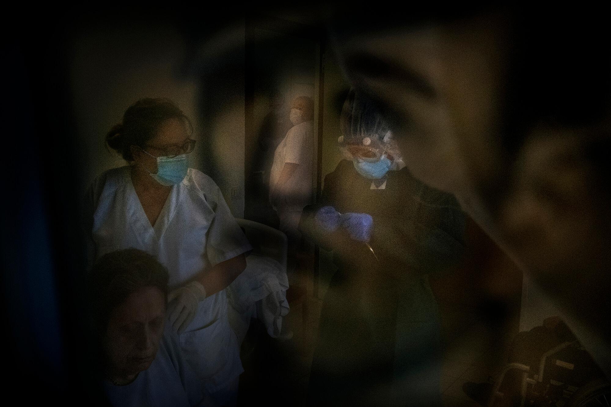 El reflex d'un familiar al vidre d'una fotografia emmarcada acompanya l'escena de dues treballadores atenent una resident.