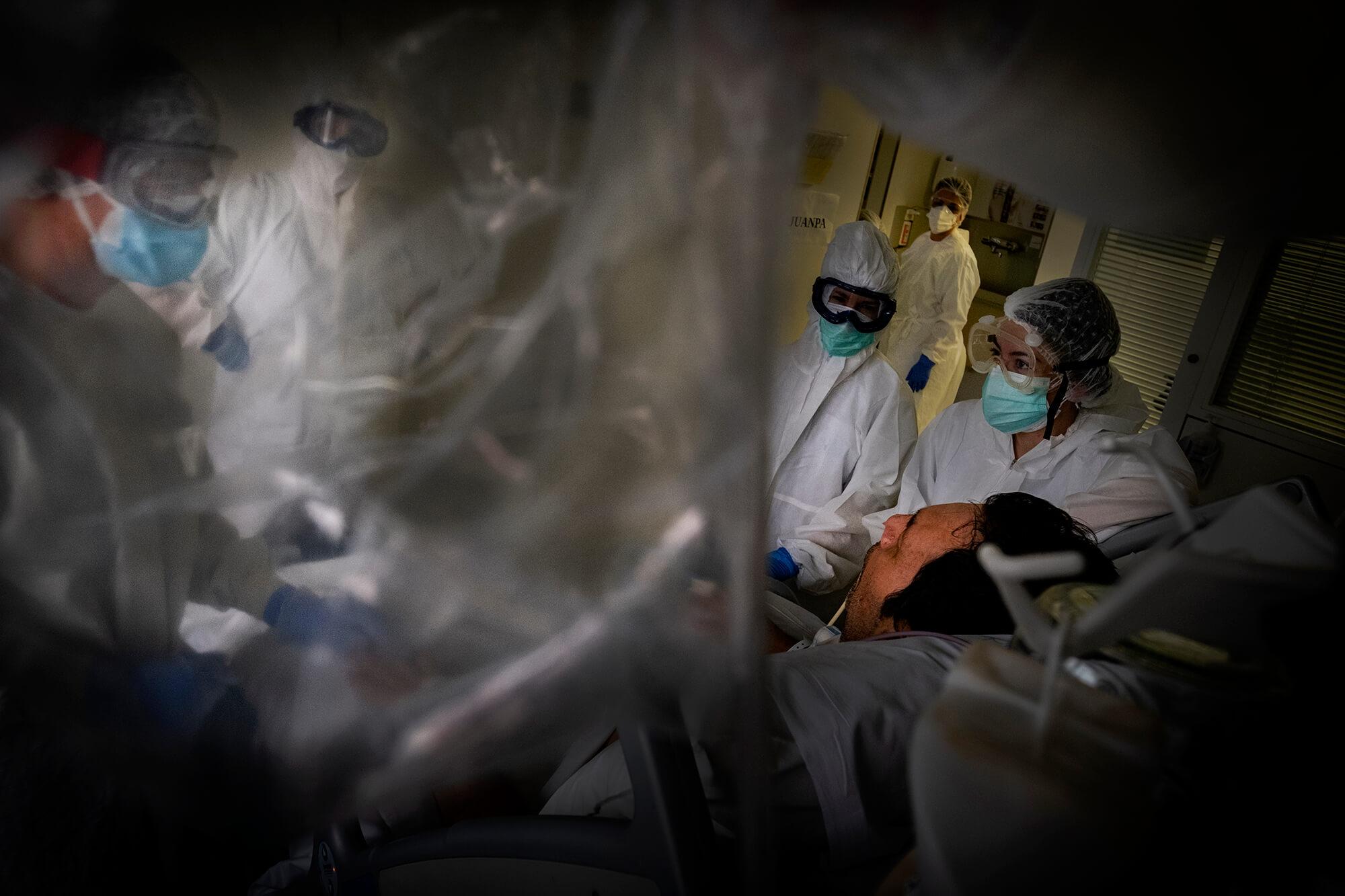 Professionals sanitaris, amb equips de protecció individual, tractant un pacient malalt de covid-19 en una UCI. Els joves també podien emmalaltir greument.