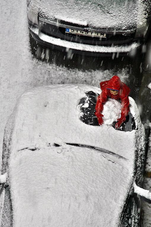 Una nena juga amb la neu a la sortida de l'escola, al centre de Cornellà de Llobregat.
