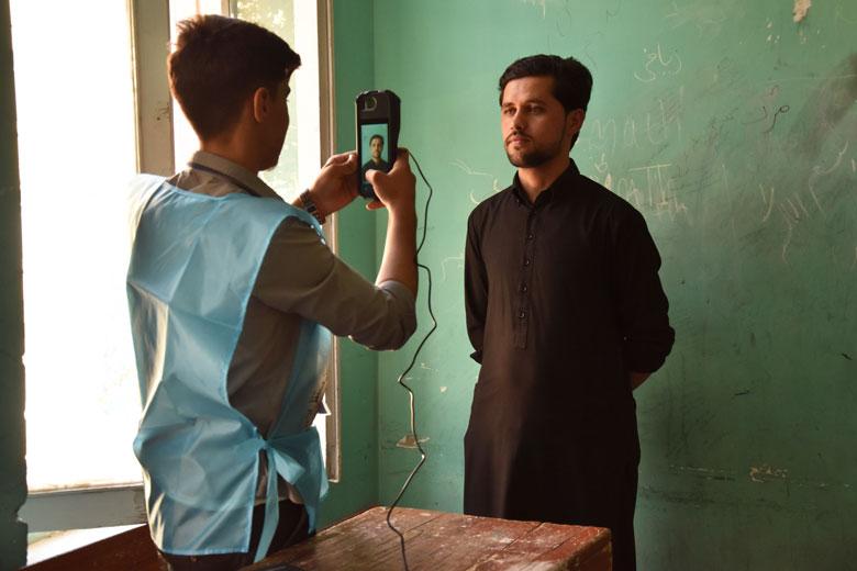Un treballador electoral pren una fotografia a un votant amb una màquina biomètrica, ahir a Kabul.