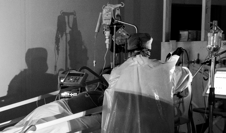 Una sanitària atenent un malalt a la UCI de l'Hospital Parc Taulí de Sabadell