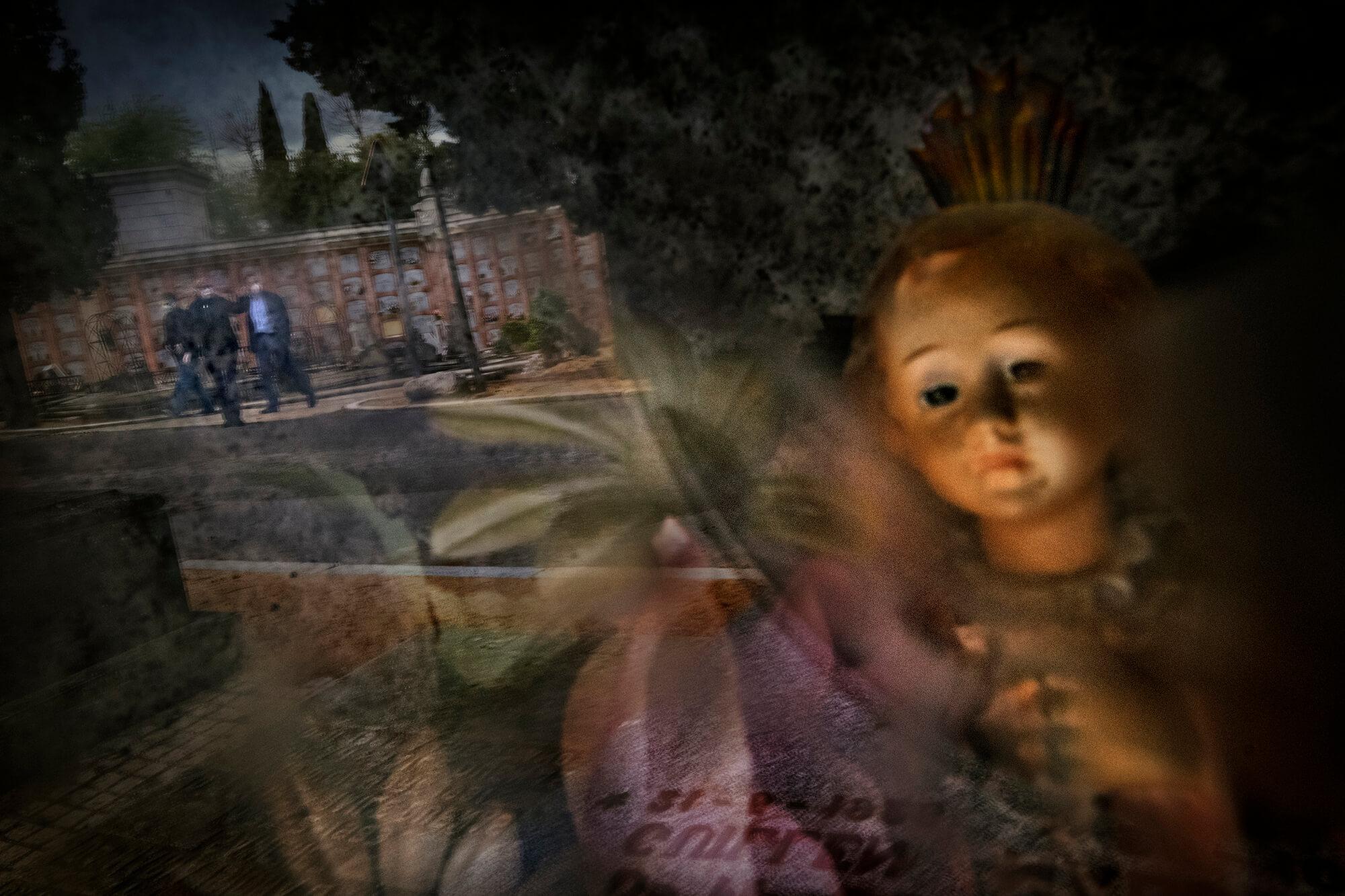 Diversos familiars protegits amb mascaretes visitant el cementiri de l'Almudena, a Madrid.