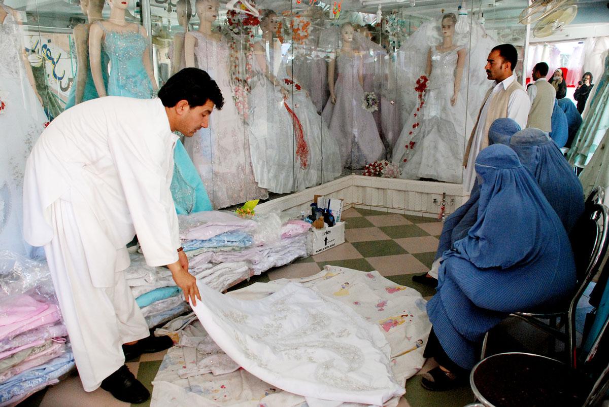 Unes dones amb burca triant un vestit de núvia en una botiga a la ciutat afganesa d'Herat.