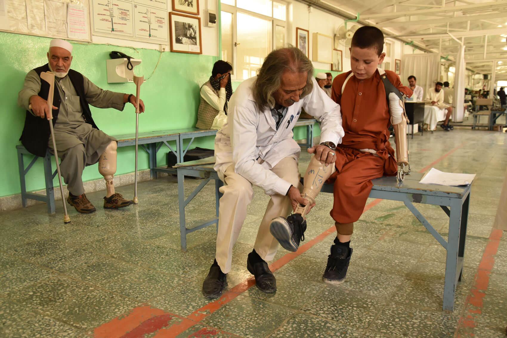 Un terapeuta posa la pròtesi a Farshid al centre de rehabilitació que el Comitè Internacional de la Creu Roja té a Kabul.